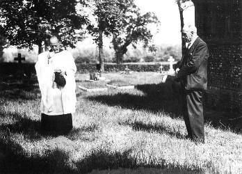 Le révérend Hemming et Harry Price se recueillant sur la tombe de la nonne à Liston